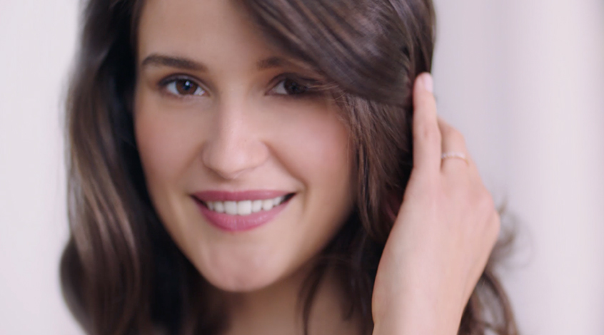 Woman with brown hair and brown eyes smiles into the camera while holding her hair back