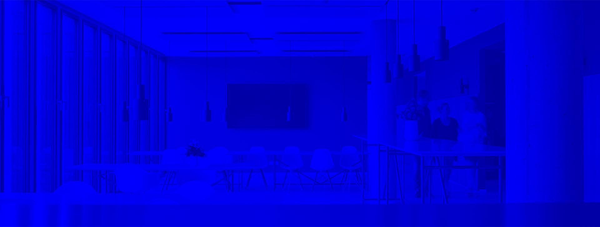 Raum mit Stuehlen und Tischen mit blauem Filter