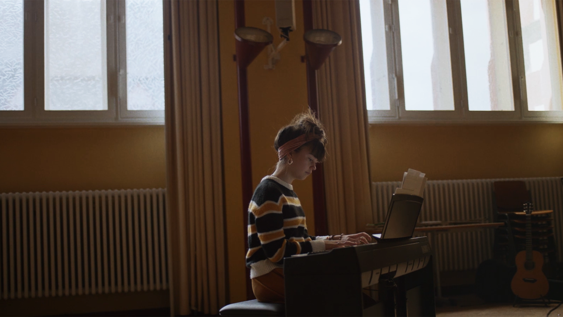 Maedchen spielt Keyboard, im Hintergrund ein Musikklassenzimmer