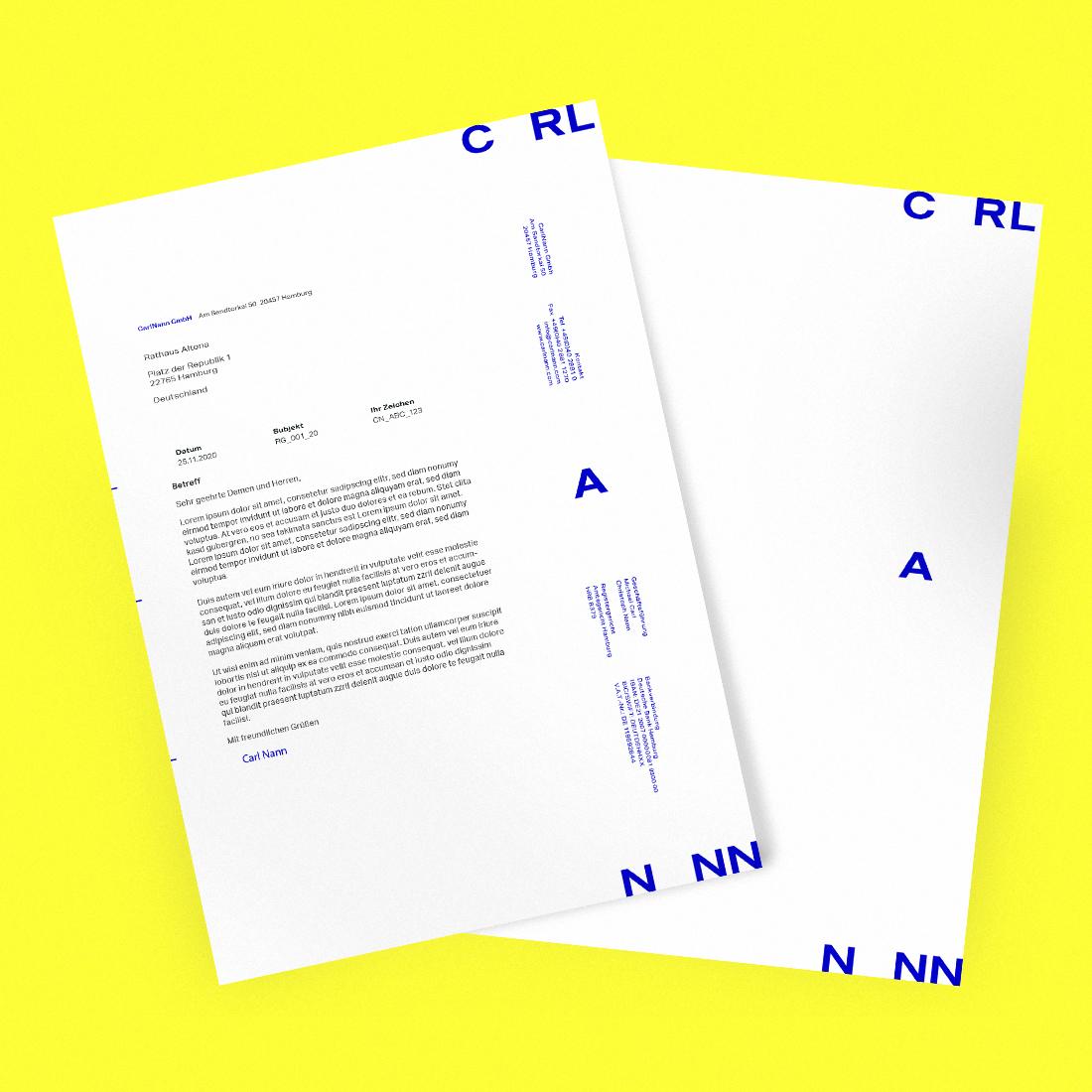 Blaues CarlNann Logo auf Dokumenten auf gelbem Hintergrund