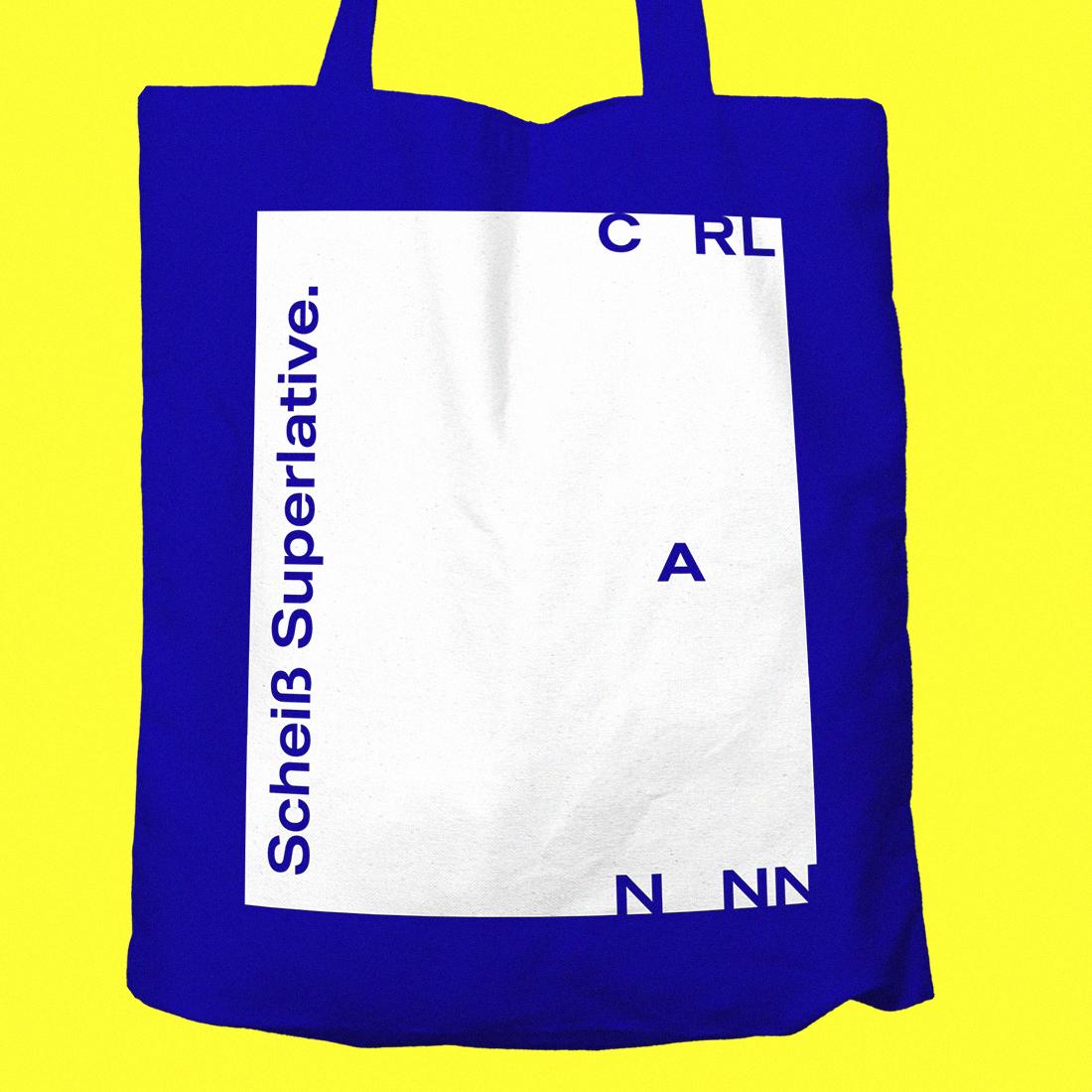 """Blauer Jutebeutel mit CarlNann Logo und """"Scheiß Superlative"""" Aufdruck auf gelbem Hintergrund"""
