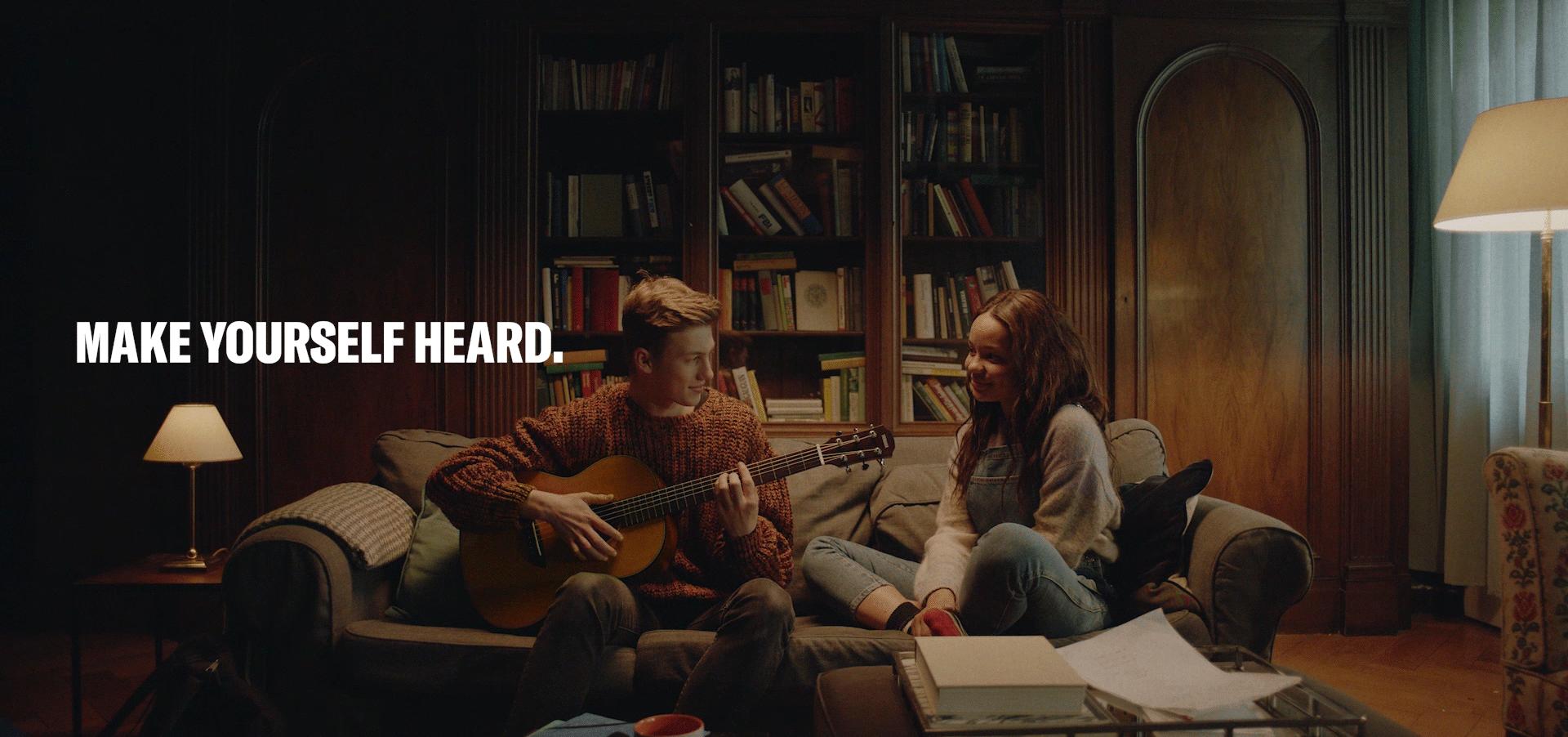 Junge spielt Gitarre und sitzt auf Sofa mit Mädchen