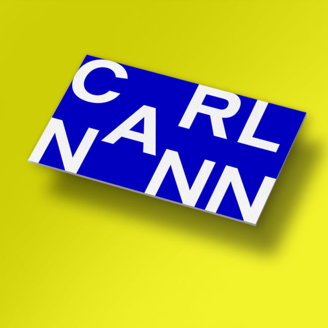 white CarlNann Logo on blue square in front of yellow background