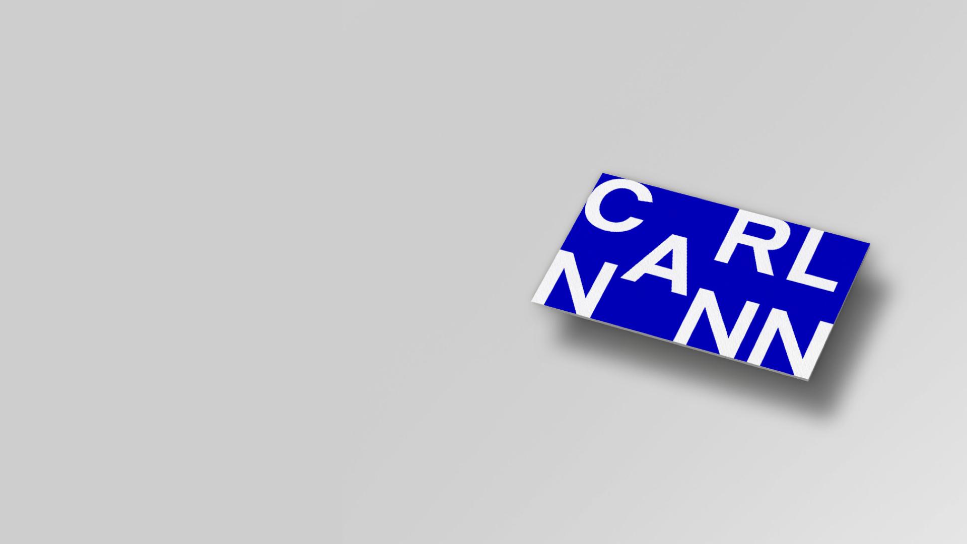 White CarlNann Logo on blue square on grey background