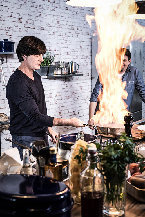 Jogi Löw cooking, holding a pan inside his hands, pan has flames coming out of it