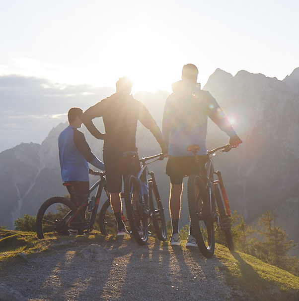 Three men are standing next to their bicycles in the mountains and are looking into the sun