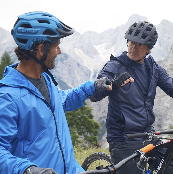 Two men sitting on their bicycles in the mountains wearing helmets