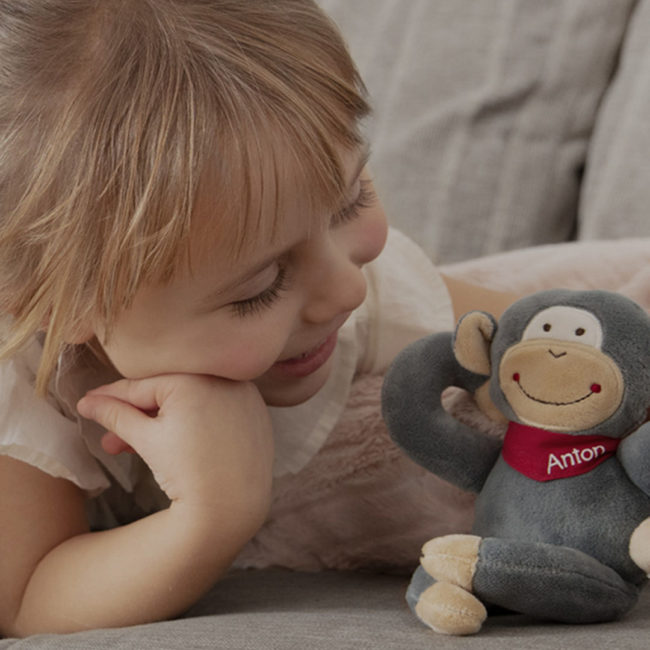 Blonde girl is playing with stuffed animal Anton on the sofa