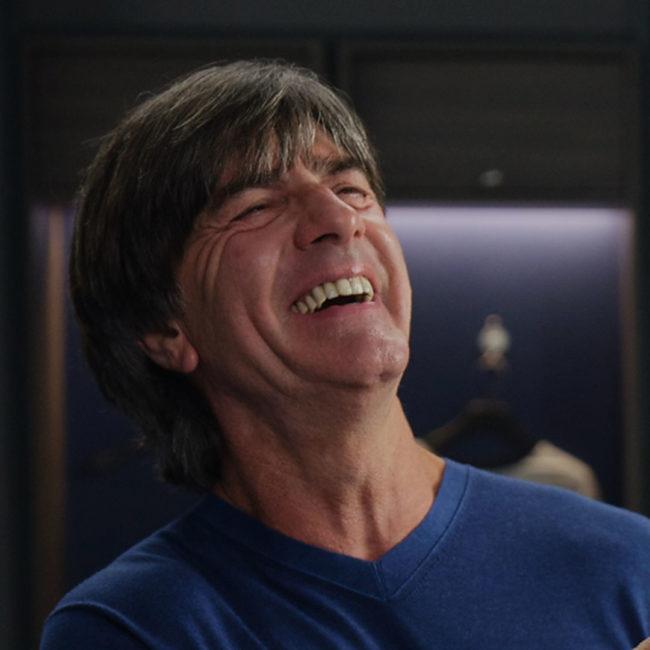 Jogi Löw wearing blue shirt and laughing