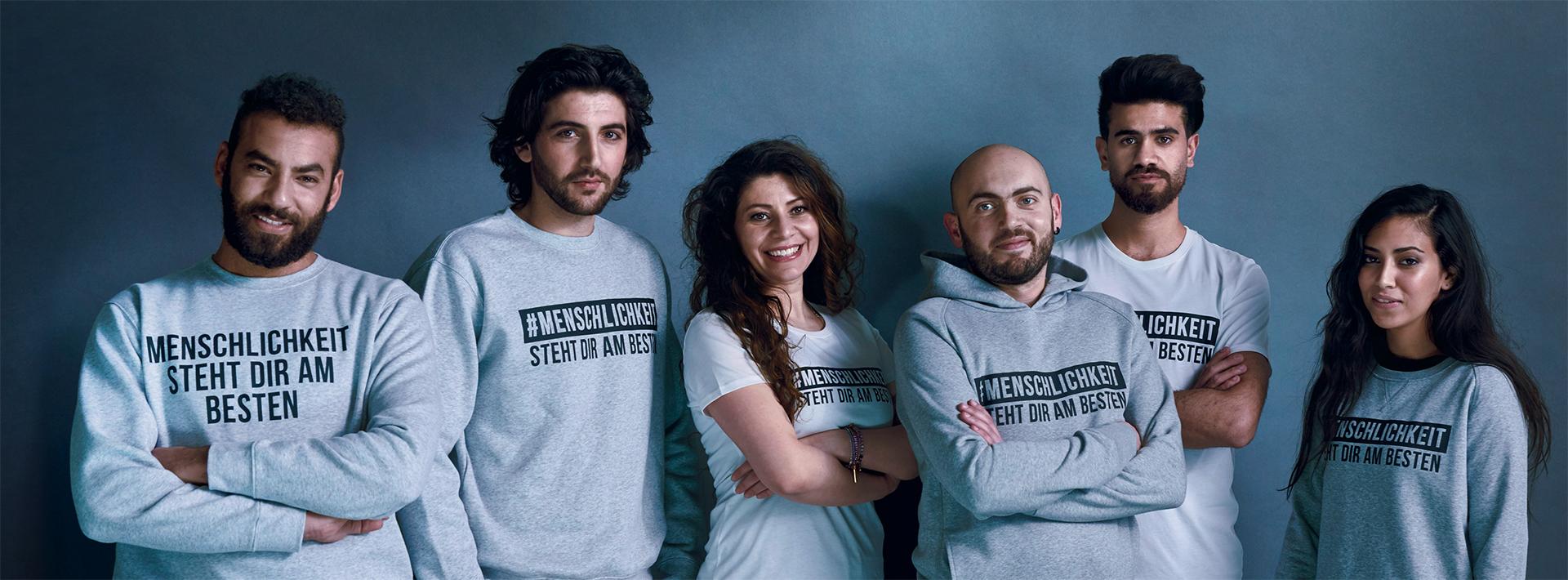 Models tragen Shirts und Pullis mit Aufdruck #Menschlichkeit steht dir am besten vor grauem Hintergrund